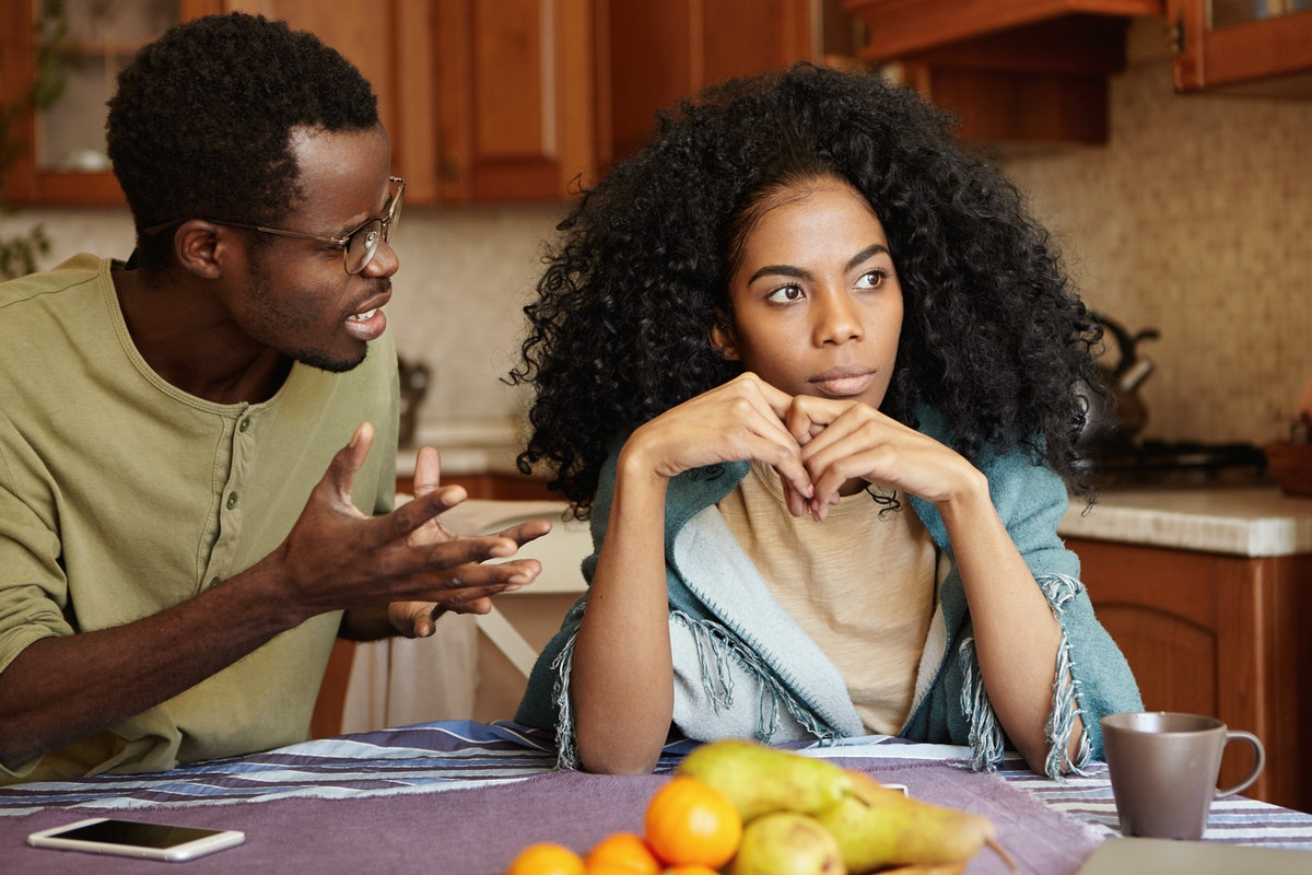 Furious black male gesturing in despair or anger while trying to make excuses to his offended wife as if saying: Can you just hear me out? African couple going through hard time in relationships