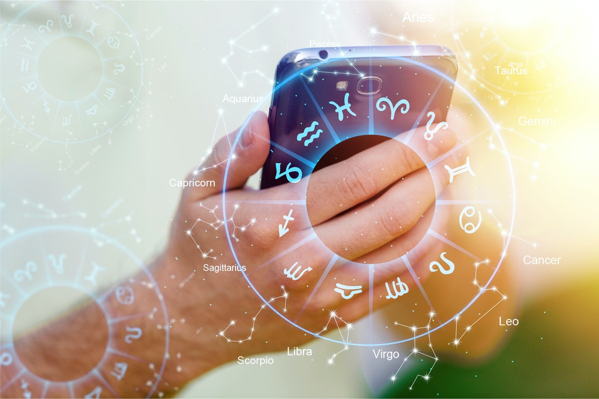 Astrology smartphone app concept, woman using mobile phone, close up of hands          - Image