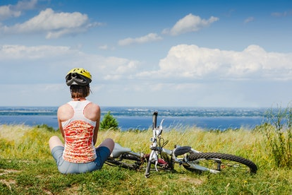 Girl cyclist with bike relax front view panorama of the sunny spring park