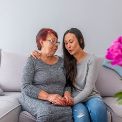 Love of mother and daughter. Smiling mother and daughter talking on couch at home. Asian Mother With Daughter Sitting On Sofa At Home Chatting