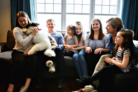 A Portrait of nice cute cheerful big family parent with the twin girls and children with bobtail dog