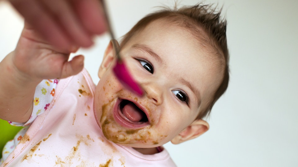 instant pot baby food recipes; baby eating pureed food in a high chair