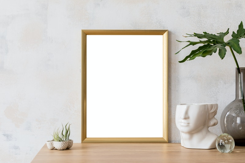 Modern and eclectic room interior with abstract wiped walls, gold mock up frame head sculpture, air plants, vase with leaf .Stylish space with design accessories. Stylish home decor. Real photo.