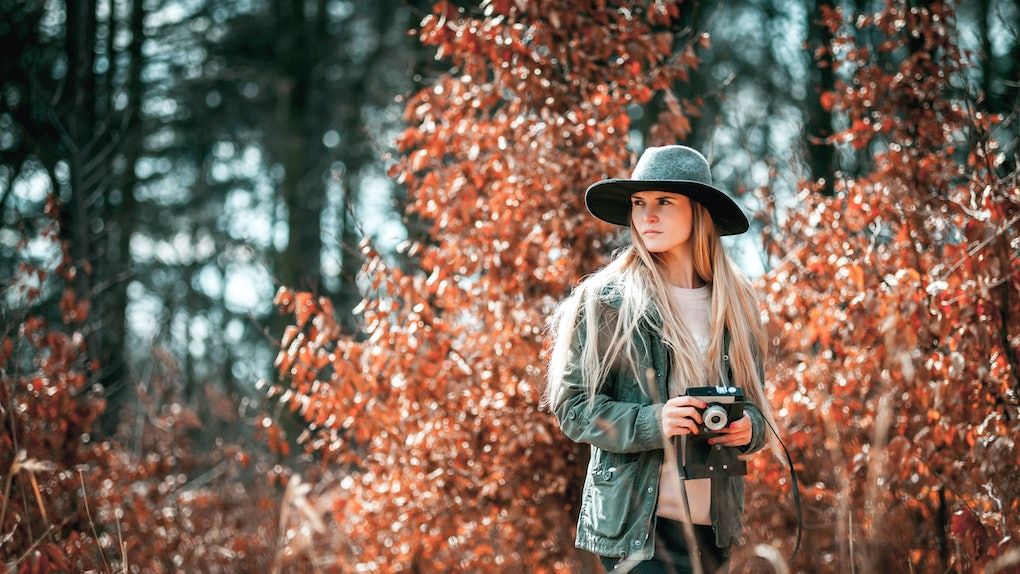 Beautiful girl with vintage camera in golden autumn forest
