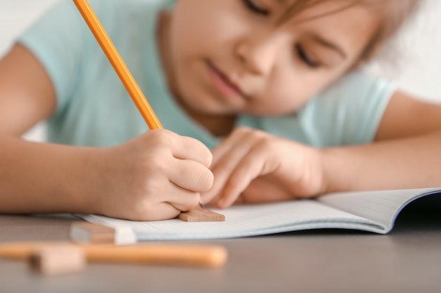 Cute little girl doing homework, closeup