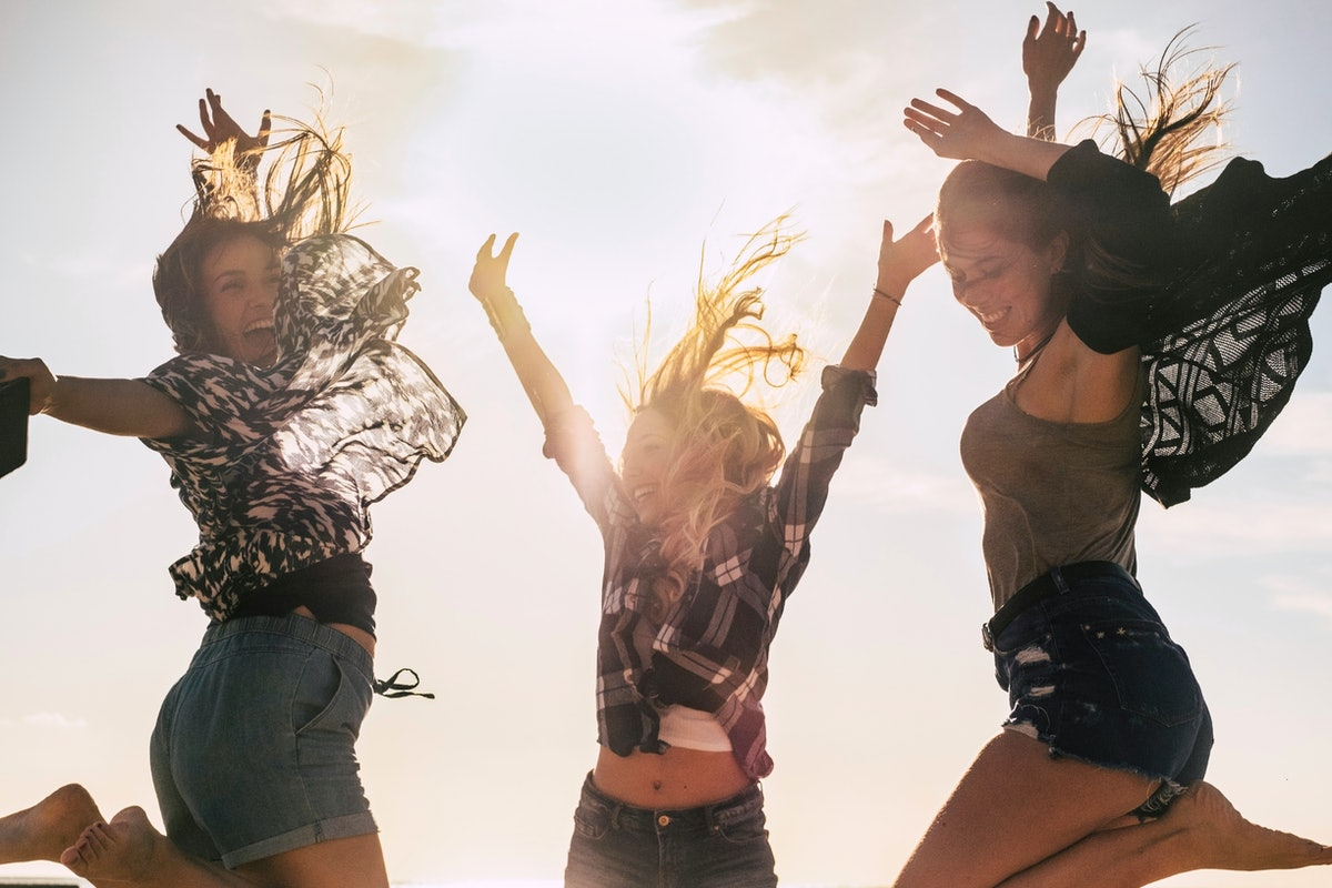 Happy young people concept youthful girls jumping and laughing together in friendship - celebration with sunlight in backlight - beautiful women and joyful