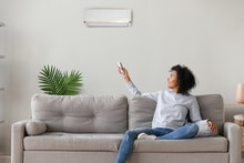 Smiling young African American woman using air conditioner, cooler system remote controller, switchi...