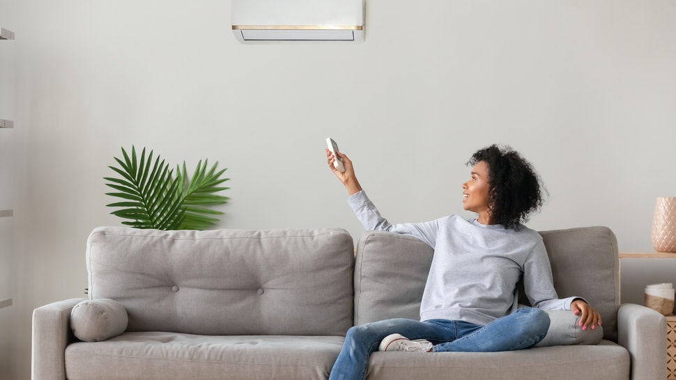 Smiling young African American woman using air conditioner, cooler system remote controller, switching, setting comfort temperature in living room, resting on cozy sofa at home, enjoy fresh air