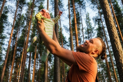 Happy bearded father holding his 3 months old sleepy baby boy on his outstretched arms.