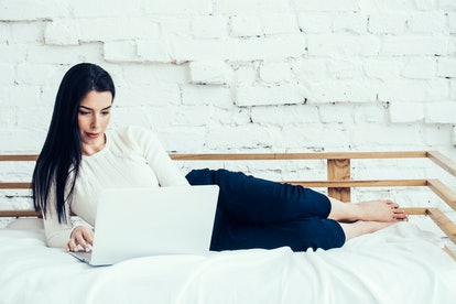 Woman with laptop on bed home natural lifestyle portrait