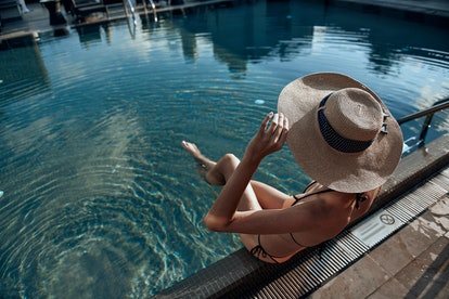 Cropped photo of Caucasian woman wearing sunhat and situating in the swimming pool. Summertime conce...