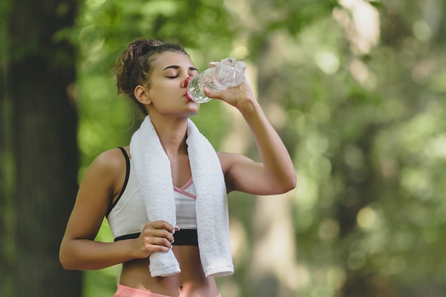 Beautiful young woman drinking water and cooling off after her running training at the park