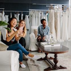Women taking photographs of a female friend trying on wedding dress. Women in wedding dress fitting ...
