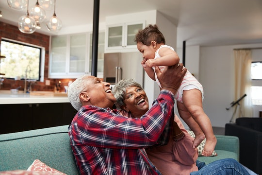 Grandparents Sitting On Sofa Playing With Baby Granddaughter At Home
