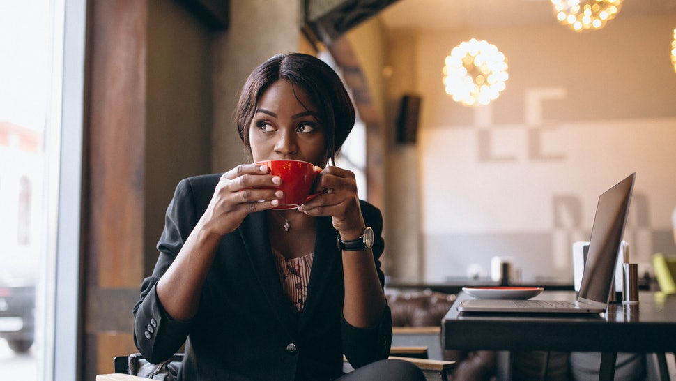 African american business woman drinking coffee in a bar