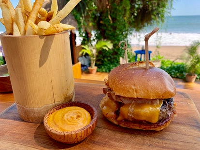 Brioche cheese burger with meat and BBQ rib meat, french fries and spicy mayo on a wooden presentation board with beautiful tropical sea view, bali vacation food
