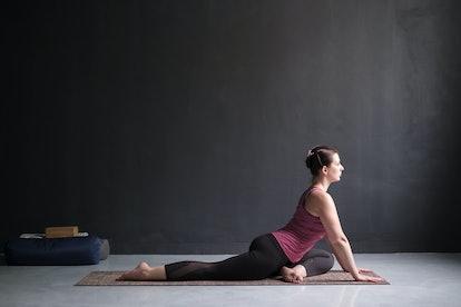 Young woman working out doing easy variation of One Legged King Pigeon Pose, Eka Pada Radjakapotasana. Full length on black background