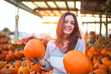 Fashionable beautiful young girl at the autumn pumpkin patch background. Having fun and posing. Tone...