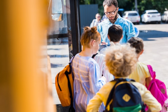 rear view of pupils entering school bus while teacher writing in clipboard