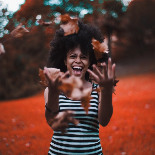 Curly laughing African-American girl in a striped dress is fooling and throwing up a heap of dry autumn leaves, with forest and meadow in unnatural vivid red colors behind, strong teal bokeh