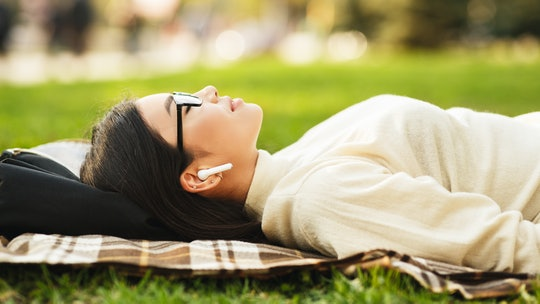 Girl listening music in airpods with closed eyes, lying on blanket in park