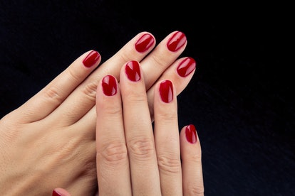 Pretty red painted short nails and hands isolated on black background