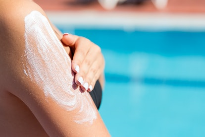 Attractive girl in sunhat applying sunscreen on shoulder by the pool. Sun Protection Factor in vacation, concept.