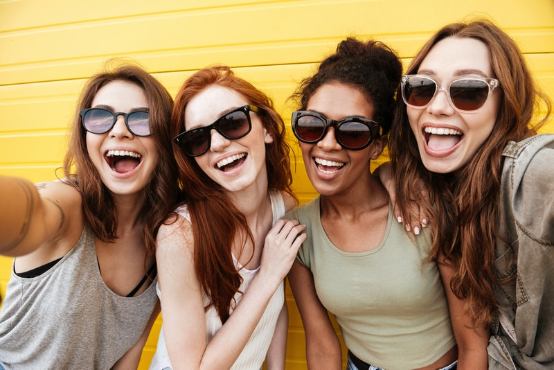 Image of young happy women friends standing over yellow wall. Looking at camera make selfie.