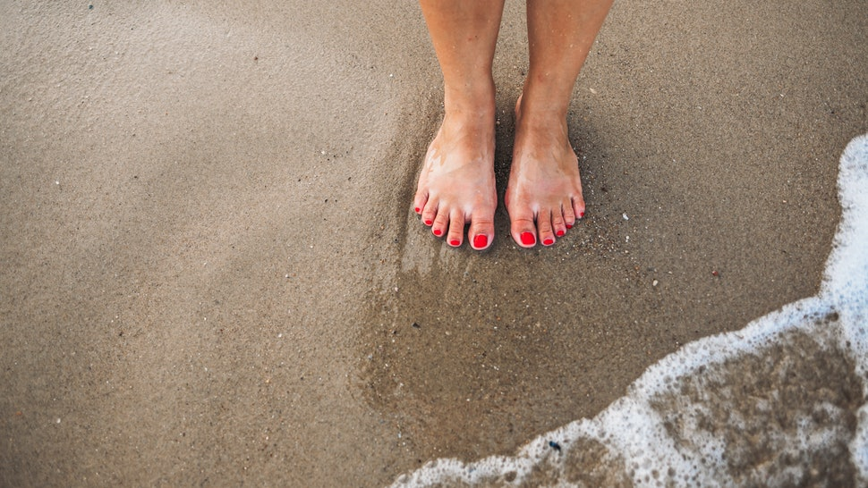 Female feet with red polish on nails on the beach