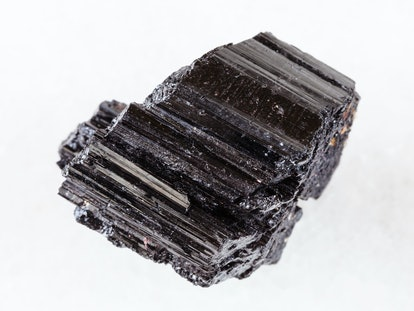macro shooting of natural rock specimen - raw crystal of black Tourmaline (Schorl) gemstone on white marble background