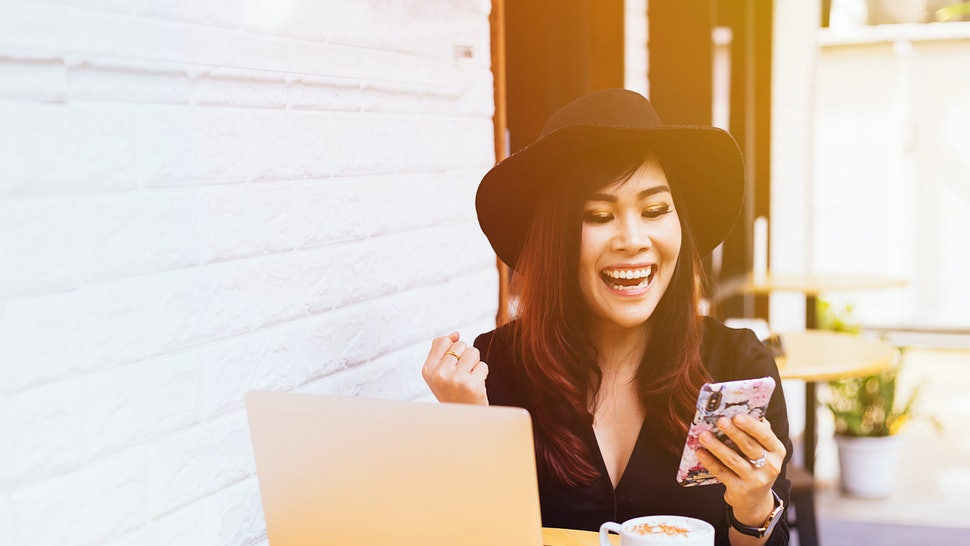 Young fashionable business woman watching her smart phone in excited and successful moment at cafe restaurant
