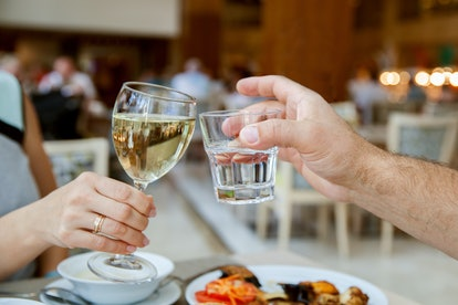 Man and woman are clanging glasses in restaurant