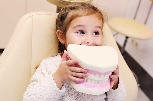 baby girl smiling sitting in dental chair with artificial jaw in hands