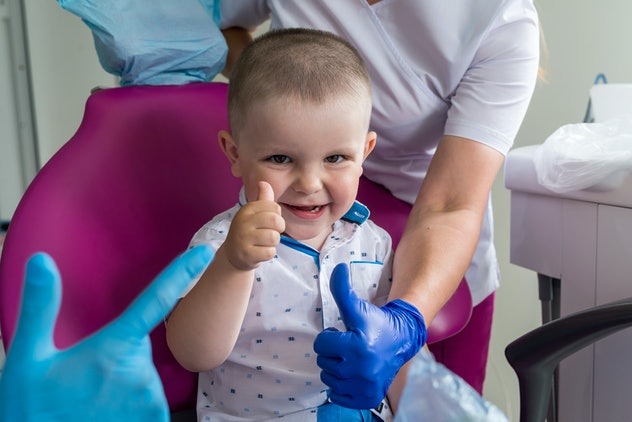 Little boy in dentistry smiling and showing thumb up