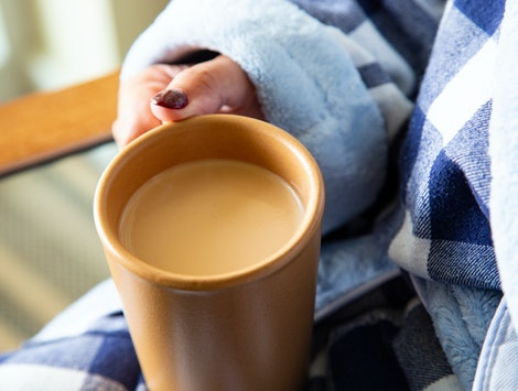 Close up of a woman holding a cup of coffee in a robe