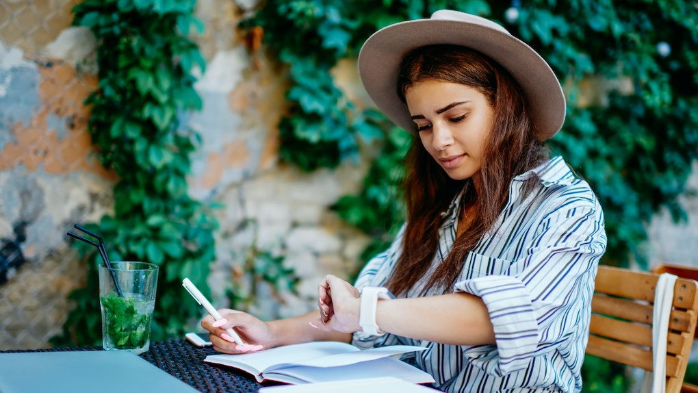 Pensive female blogger writing in notebook checking notification on modern designed wearable computer, creative caucasian hipster girl making to do list and using organizing app on smartwatch