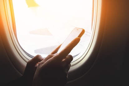 Hand using smart phones on board of an airplane near window seat and wing.