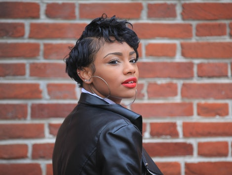 Beautiful African American girl, brunette woman looking and smiling standing at autumn or spring forest outdoors wearing black leather jacket, on the background wall of bricks, lips and lipstick afro