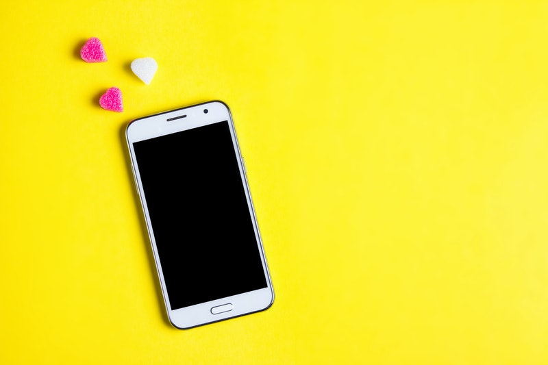 Top view of mobile cellphone and pink heart on art paper background, copy space. Mockup template for Valentines Day. Love, technology concept. Top view, flat lay.