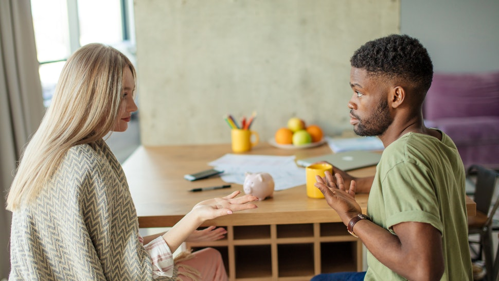 Caucasian blonde woman has some misunderstanding with her african hipster boyfriend, who is having surprised and puzzled look, couple is sitting in cozy living room with modern interior.