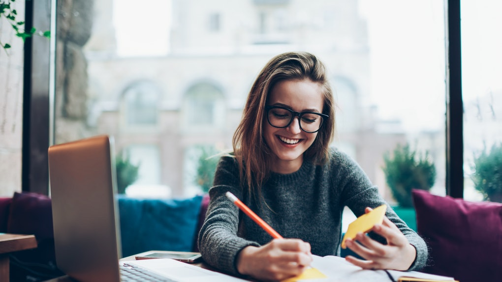 Positive female student in trendy eyeglasses enjoying time with modern notebook at coworking space, young exited hipster girl writing article review of visiting cafeteria in textbook for blog