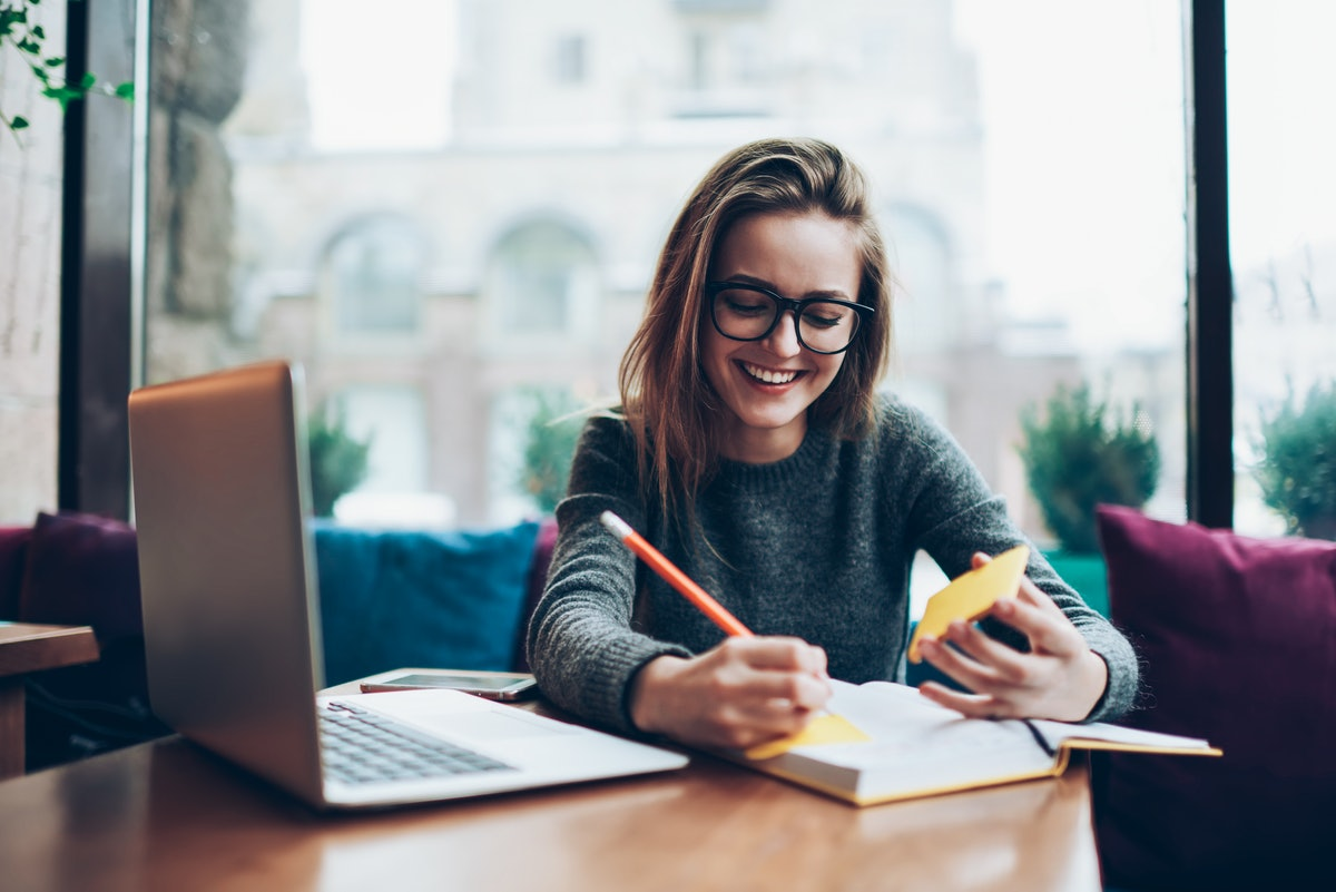Positive female student in trendy eyeglasses enjoying time with modern notebook at coworking space, ...