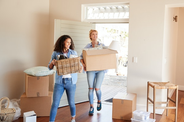 Female Friends Carrying Boxes Into New Home On Moving Day