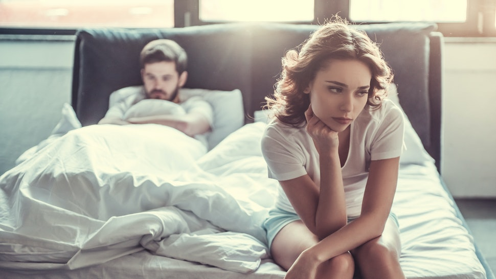 We have a problem. Young upset girl sitting on the edge of the bed, against her boyfriend, lying in bed.