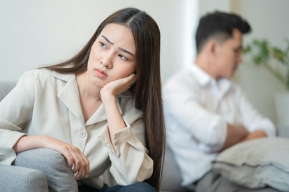 Young couple in quarrel at home.sadness young Asian woman sitting on sofa with boyfriends.relationship problems between couples and communication issues concept