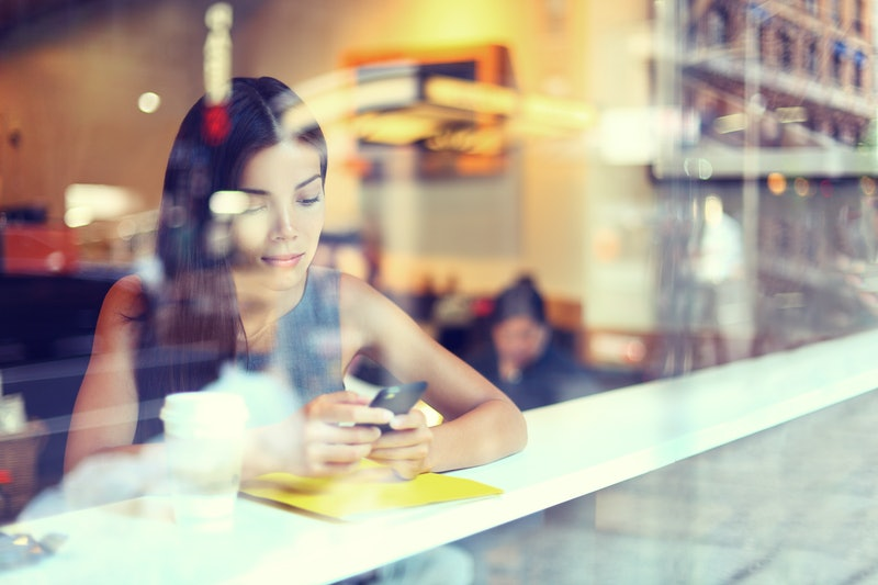 Cafe city lifestyle woman on phone drinking coffee texting text message on smartphone app sitting in...