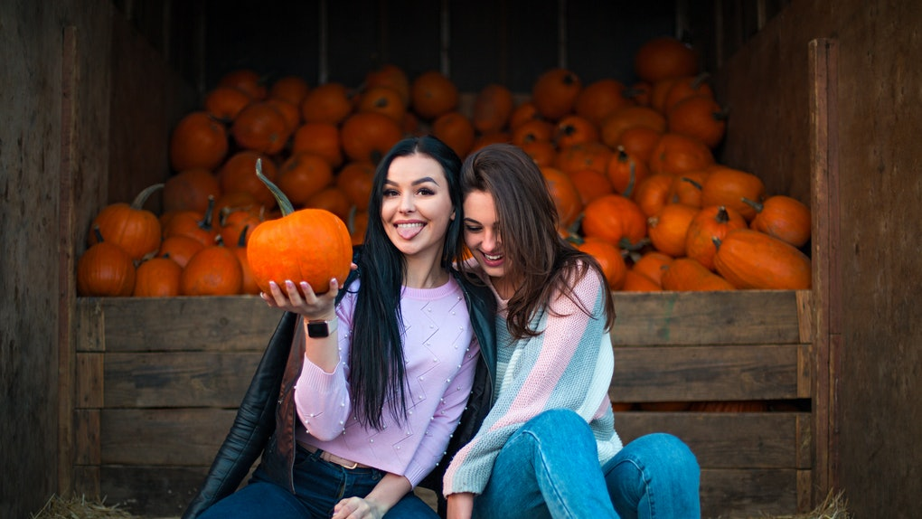 Instagram captions for pumpkin patch photos are perfect for  these two girls in jeans sitting next to each other in front of pumpkins.