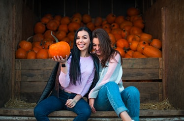 Instagram captions for pumpkin patch photos are perfect for  these two girls in jeans sitting next t...