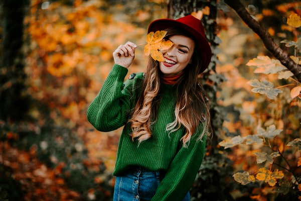 Outdoor autumn portrait of beautiful girl /model /fashion blogger/travel blogger smiling with long hair wearing hat and stylish clothes surrounded by yellow and orange leaves.