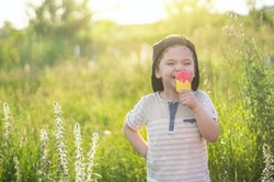 Happy Child eating cookies in the form of ice cream. Kids eat in the garden. Boy in the garden holdi...